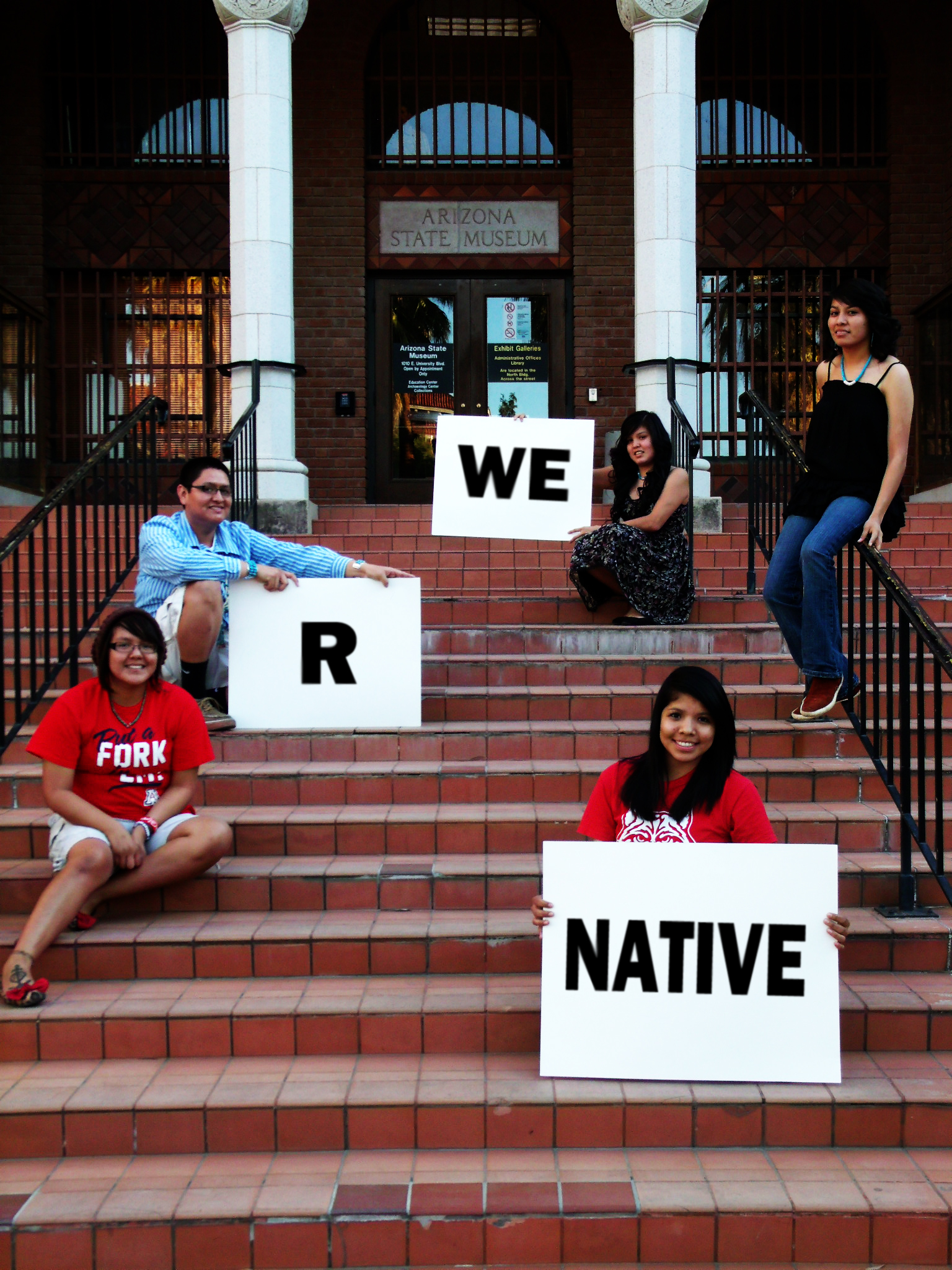 Five youth outside the Arizona State Museum holding 'We R Native' signs