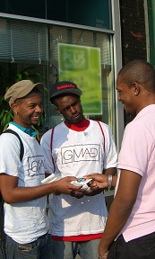 Two men in GMAD T-shirts giving information to another man