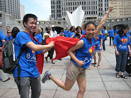 "Man and woman in ""B a hero"" T shirts and red capes in superhero pose at outdoor event"