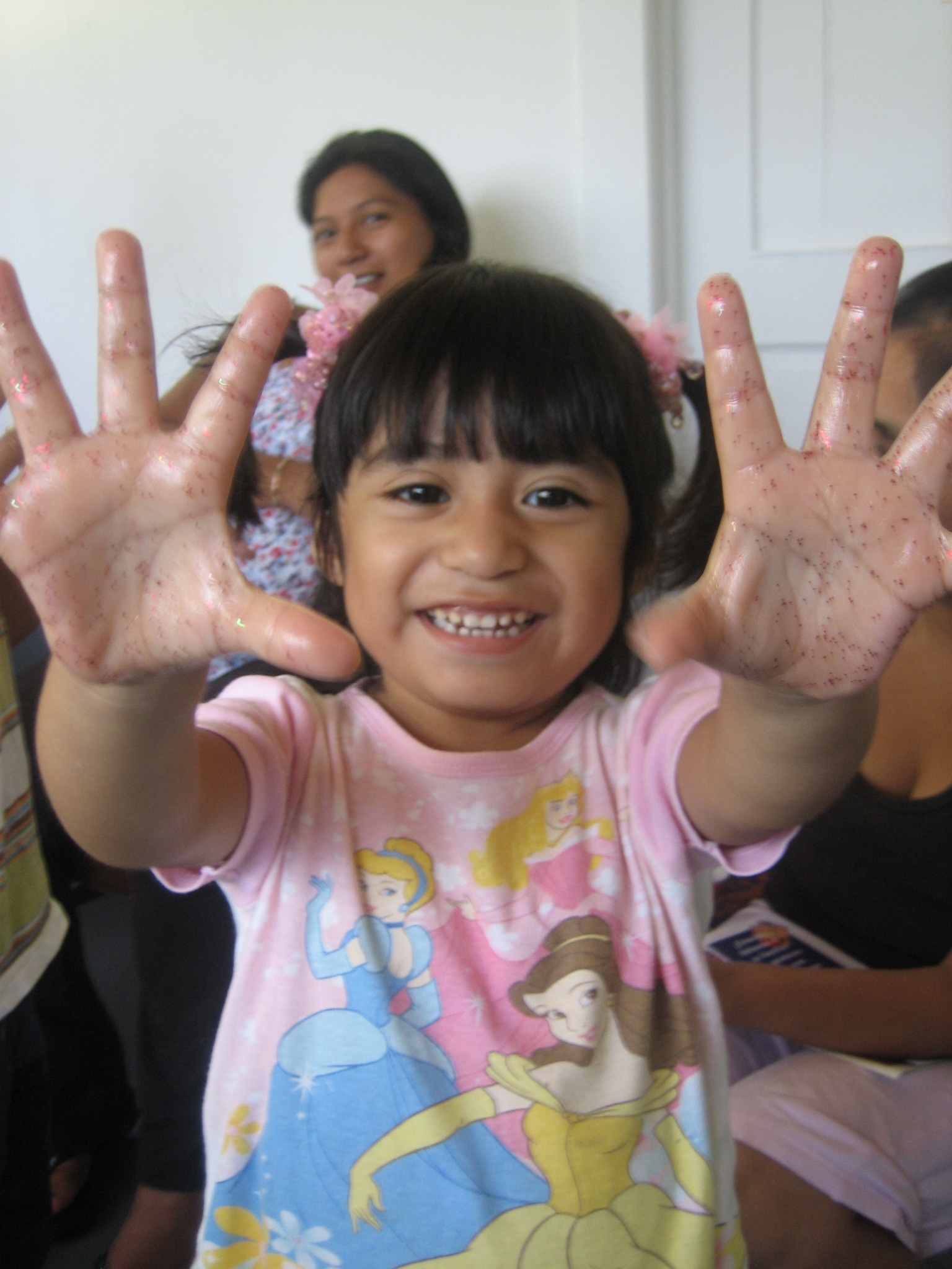 Child in a group with hands lifted up